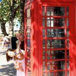 une cabine telephonique rouge avec deux enfants et une maman
