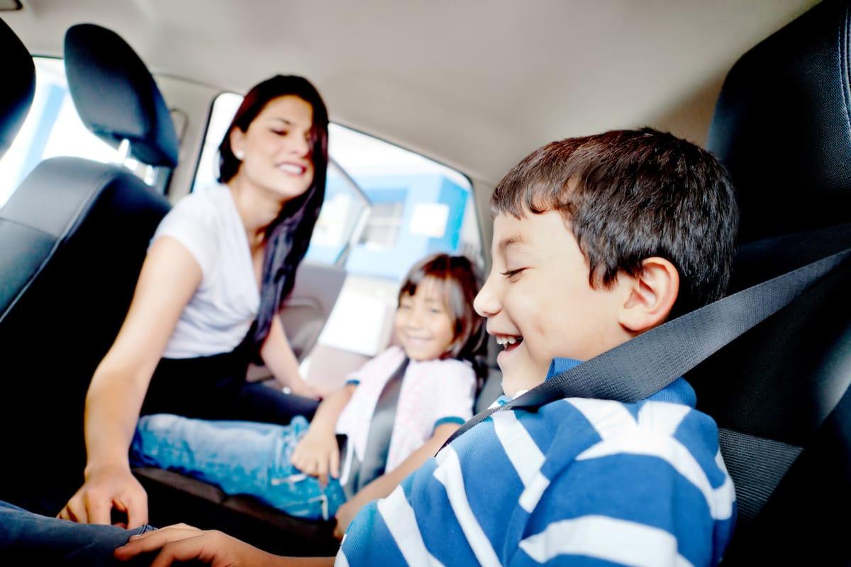parent s'occupant de mettre la ceinture de sécurité à deux enfants dans une voiture