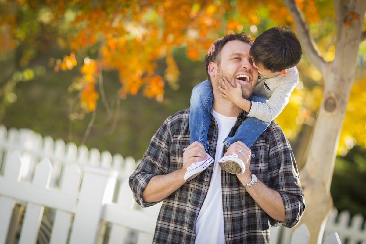 un papa portant son garçon sur ses épaules en automne