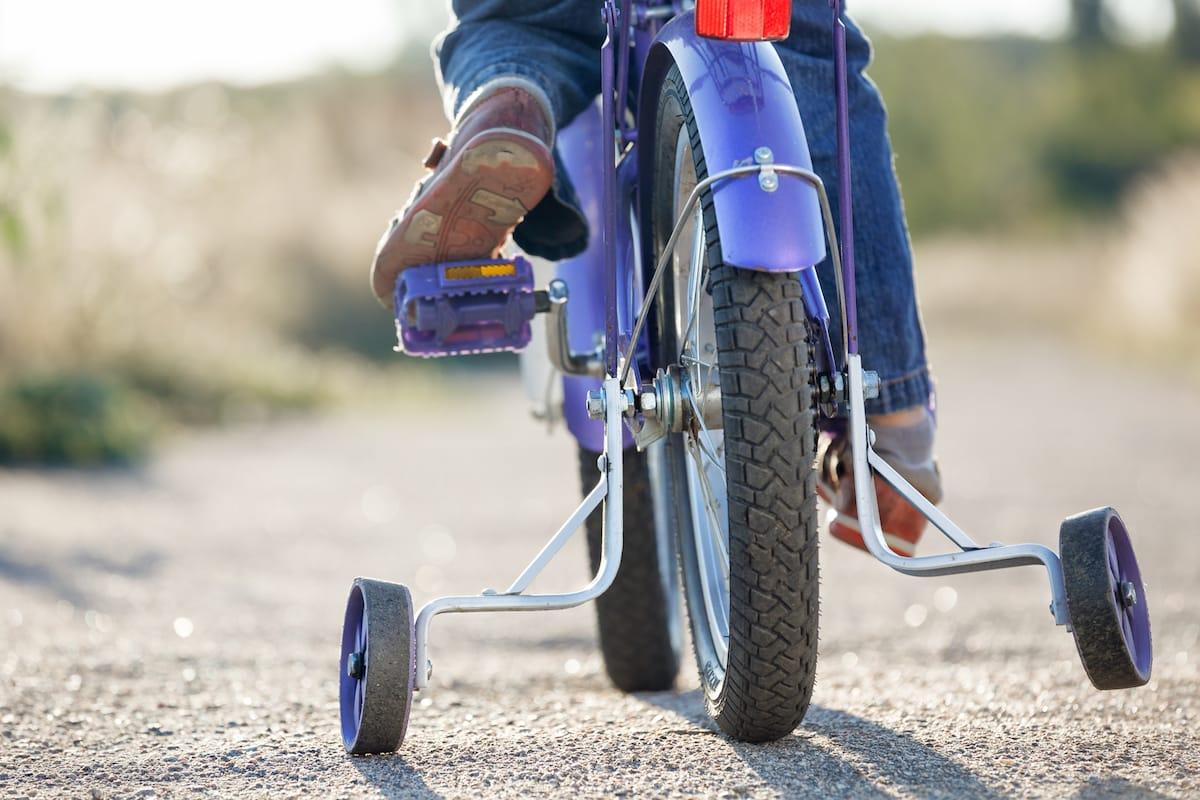roue et roulette d'un vélo enfant sur une route