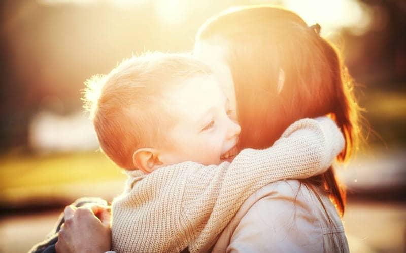 enfant serrant les bras se sa mère ambiance baigné de lumière