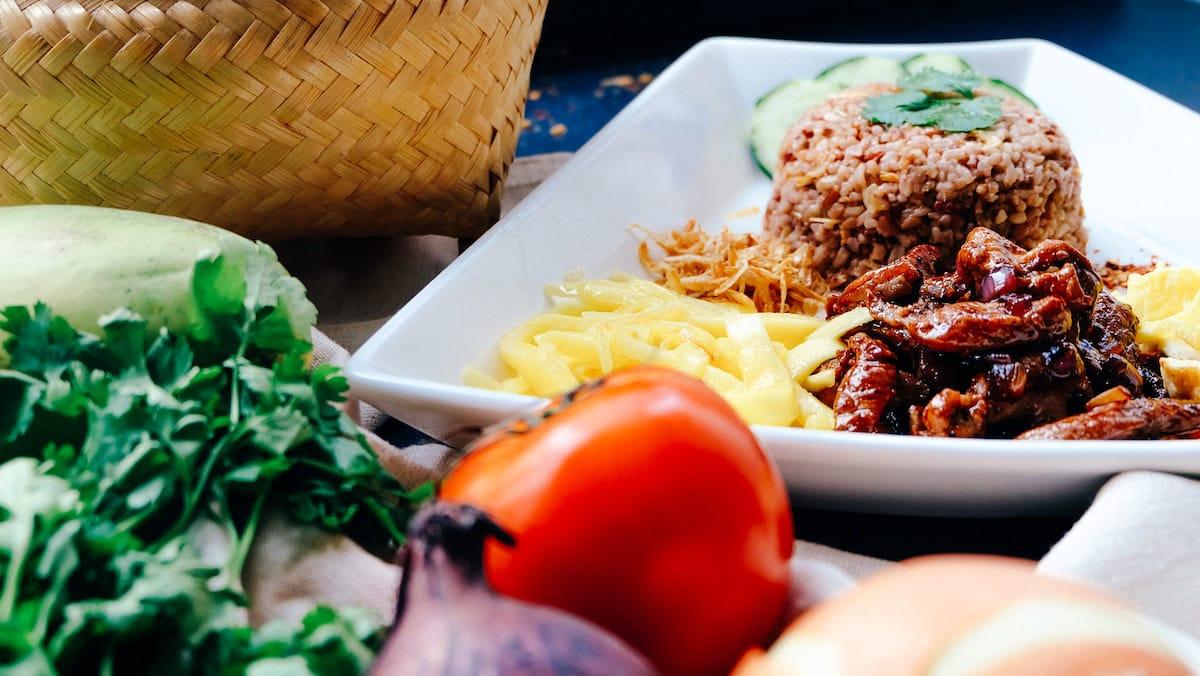 plat avec du riz en timbale, une tomate et un mijoté de viande posé à côté d'un panier en osier