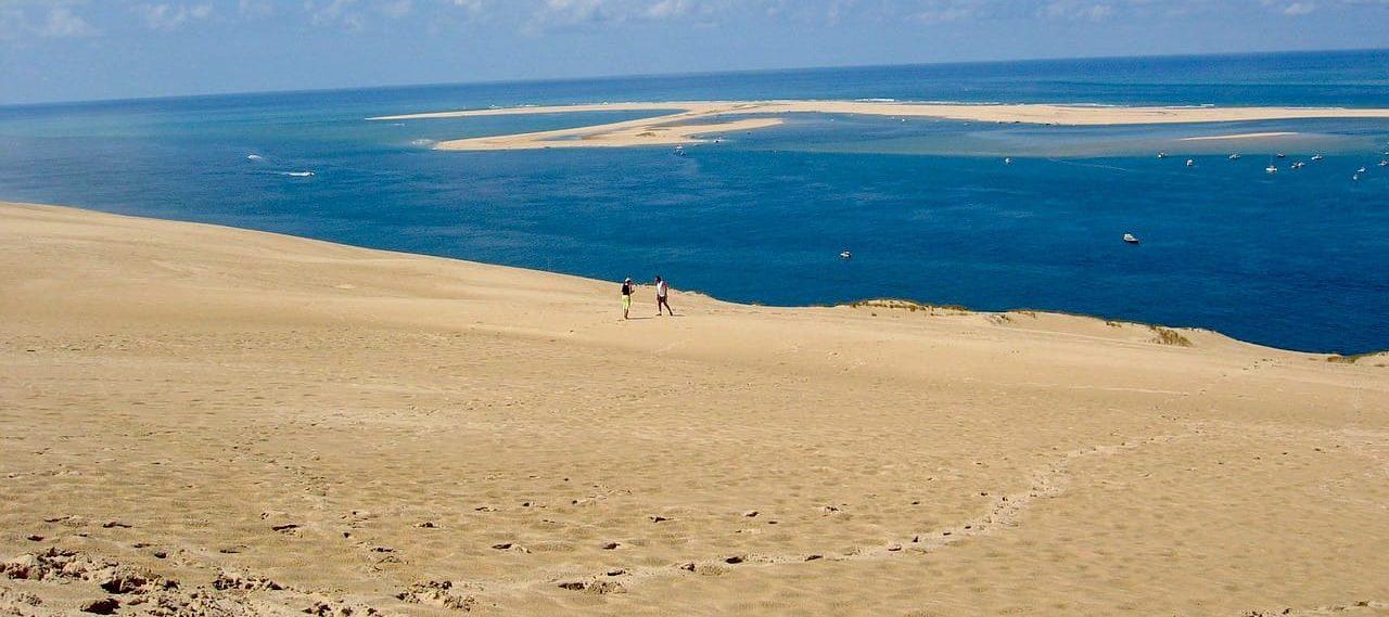 une grande dune de sable avec quelques personnes et l'océan au fond