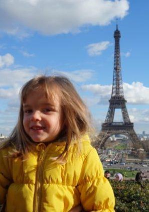 une petite fille avec une blouson jaune devant la tour eiffel au loin
