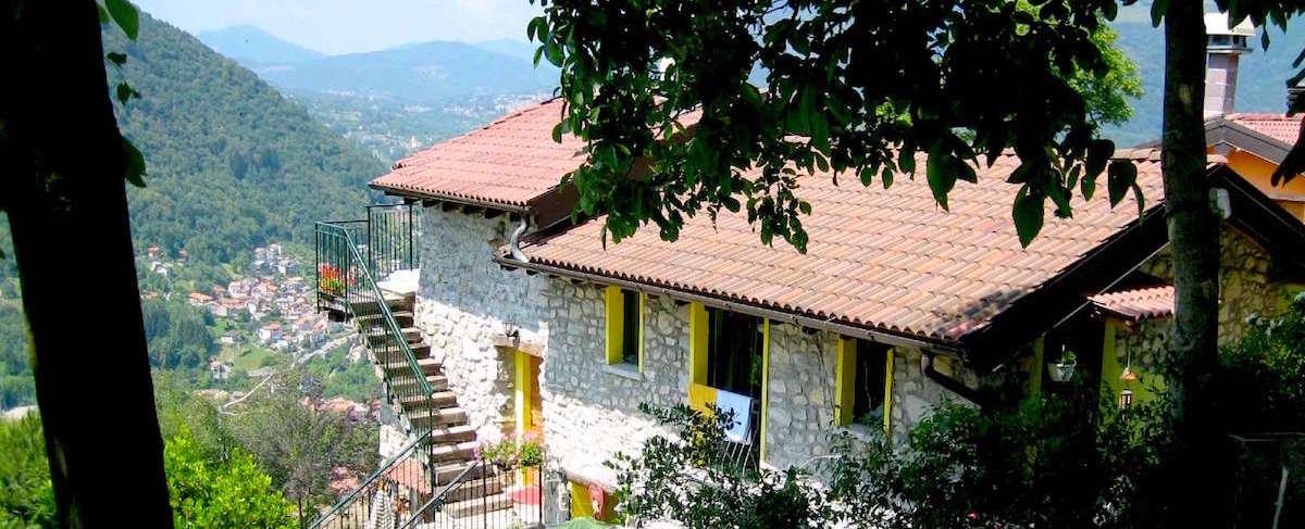 gite en pierre avec escalier extérieur donnant sur panorama montagne