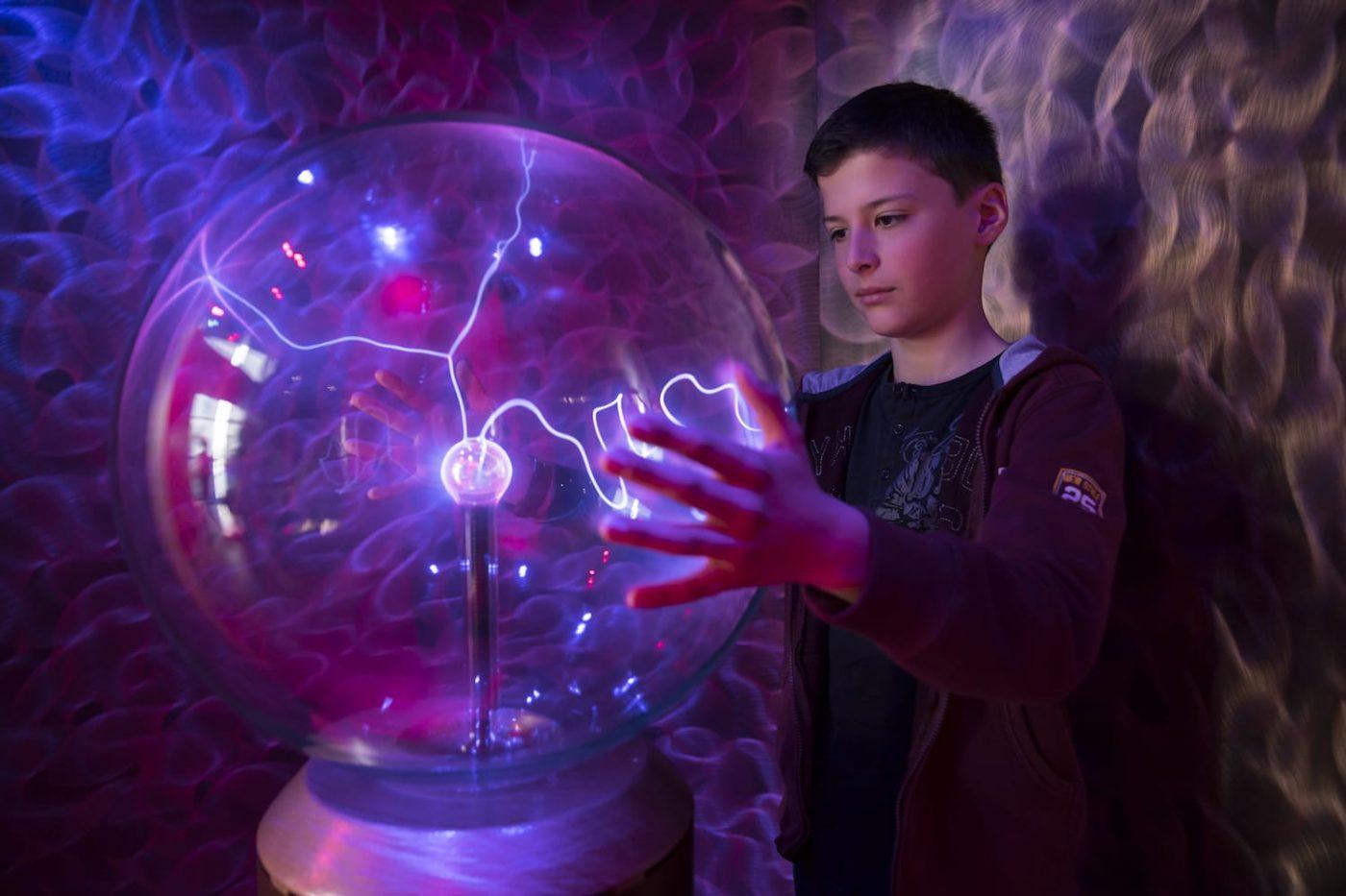 garçon mettant les mains sur un globe plasma , ambiance électrique violette