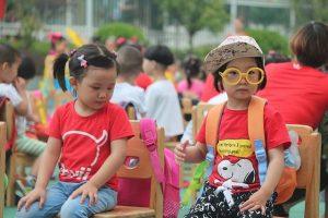 enfants chinois assis sur des chaises d'ecole à l'exterieur
